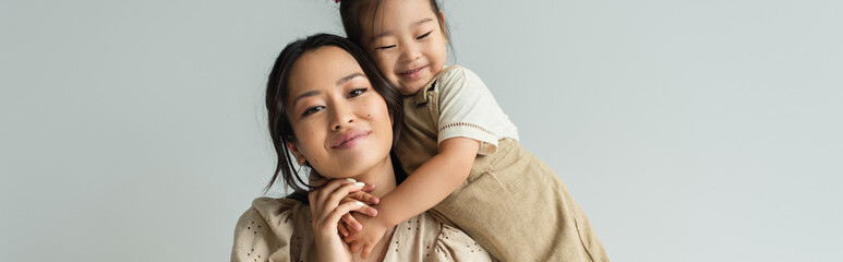 cheerful asian toddler daughter hugging happy mother isolated on gray, banner