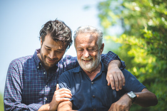 caucasian senior father and adult son are hugging together at home, generation family are happy with people love, male mature, old person man, elderly grandfather smiling living at the house