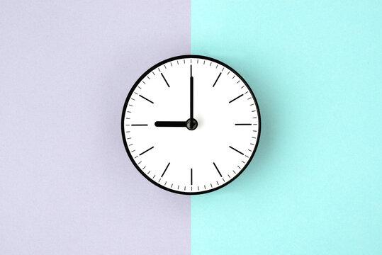 二色の色画用紙の上に置かれた時計―朝と夜の時間のイメージ