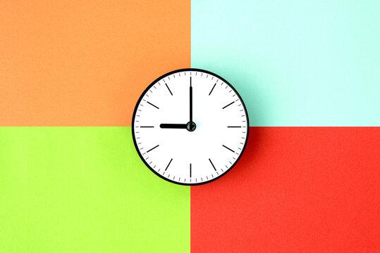 四色の色画用紙の上に置かれた時計―時間の管理と色分けのイメージ