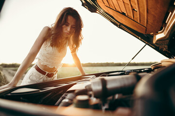 Young woman opening the bonnet of her broken car in the countryside