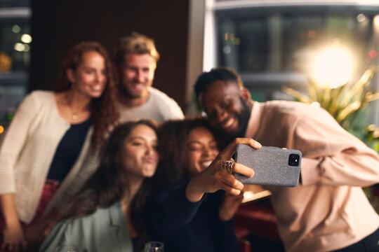 Friends in bar taking selfie on phone