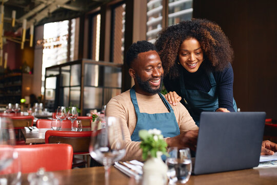 Small business owners using laptop in restaurant