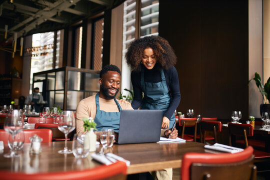 Restaurant managers working with laptop