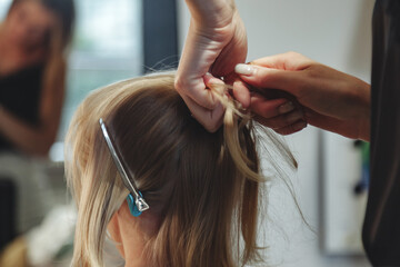Barber woman make fashionable pretty hairstyle for cute little blond girl
