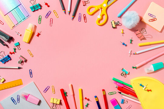 Creative student desk with school supplies and copy space in center. Top view or flat lay. Trendy back to school flat lay on pink background