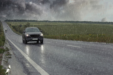 View of country road with car on rainy day