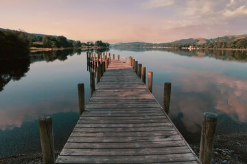 Soft pink morning light falls washes over a wooden jetty on Coniston Water in the Lake District, reflecting clouds on the surface of the lake