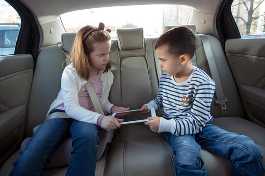 Brother and sister fighting over digital tablet on the back seat of the car