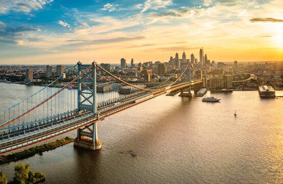 Aerial view of Ben Franklin Bridge and Philadelphia skyline at sunset. Ben Franklin Bridge is a suspension bridge connecting Philadelphia and Camden, NJ.