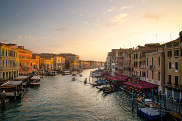 Venice sunset with a gondola on the background of the canal and buildings