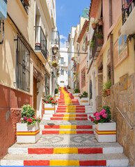 Calle Puchalt is een smal steegje in het centrum van Calpe met de trap geschilderd in de kleuren van de Spaanse vlag. Costa Blanca, Spanje