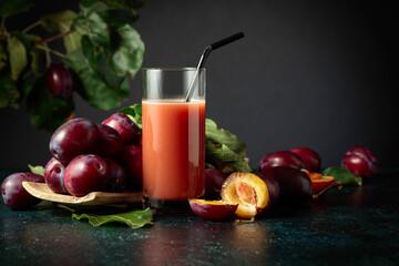 Plum juice and fresh purple plums.
