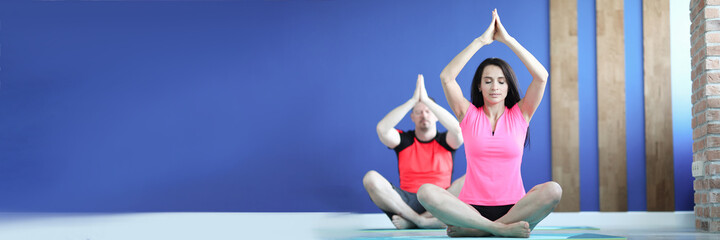 Man and woman in gym are sitting in lotus position
