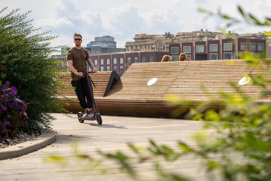 Stylish Young Man On Vacation Having Fun Driving Electric Scooter Outdoors In Modern Park.