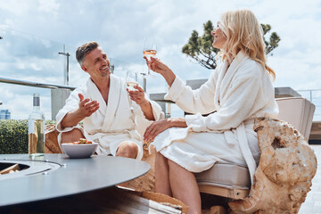 Beautiful mature couple in bathrobes enjoying fruits and wine while relaxing in luxury hotel outdoors