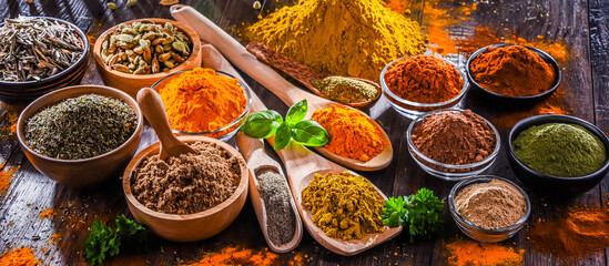 Fototapeta Variety of spices on wooden kitchen table. obraz