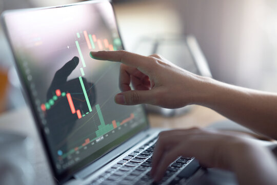 Closeup - Hand of woman is checking Bitcoin price chart on digital exchange on laptop, cryptocurrency future price action prediction.