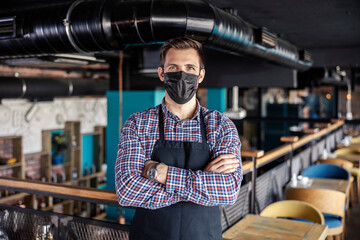 Welcome to the restaurant at the time of the corona. A male waiter with face mask stands in a cafe and wears a plaid shirt and apron. He has his arms crossed and is looking straight at the camera