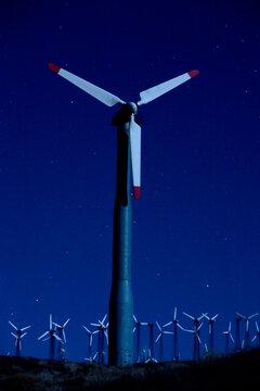 Wind turbines in landscape at night