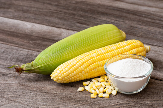 Corn starch in wooden bowl and fresh sweetcorn with kernels on wood table background.