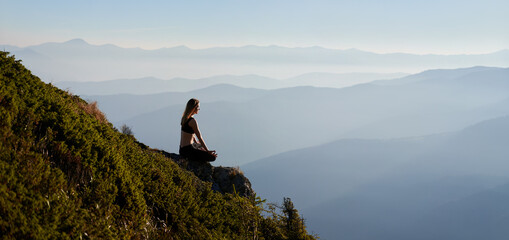 Fit young woman sitting on grassy hill in lotus position while mediating outdoors in the morning. Sporty woman doing meditation yoga exercise in the mountains. Copy space. Panorama
