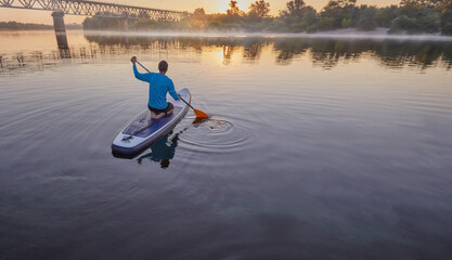 Paddleboarding. Man sitting on a SUP board in a middle of a lake and enjoying golden sunrise and fog