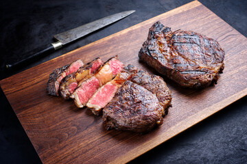 Modern style barbecue dry aged wagyu rib-eye beef steaks served as top view on a wooden design board with copy space
