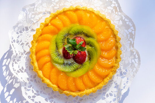 Fruit pie with fresh orange, kiwi, strawberries and cream close up on the table