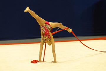 Fototapeta Gimnastyka artystyczna dziewczyna robi szpagat w pokazie z wstążkami obraz