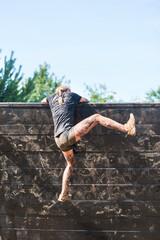 Bieg OCR kobieta wspina się przez przeszkodę