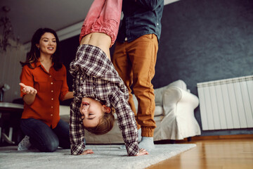 Father playing with his daughter and teaching her how to make headstand. Mother kneeling next to them and watching with smile on her face.