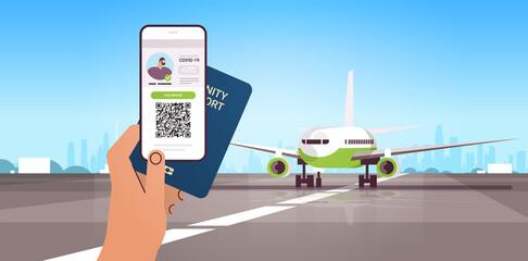 hand holding digital vaccinate certificate and global immunity passport near airplane coronavirus immunity