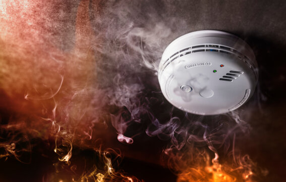 Smoke detector and fire alarm in action background