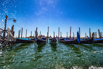 Gondolas moored in a Venice dock with water drops