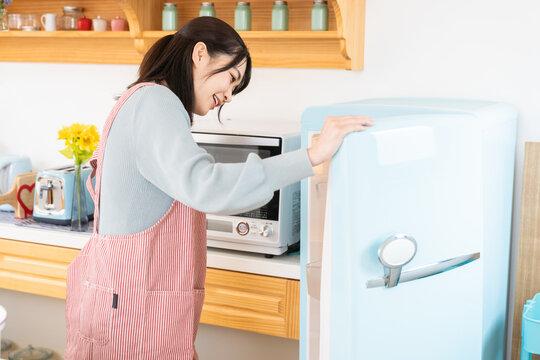 冷蔵庫の中を見る女性