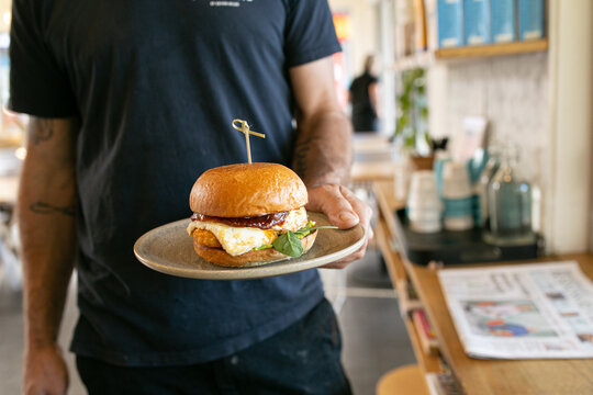 Horizontal half body shot of a man holding a hamburger on a plat in a coffee shop