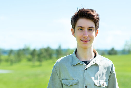 Handsome cheerful teen boy 15 years old smiling and looking at camera against blue sky and green grass at spring meadow.