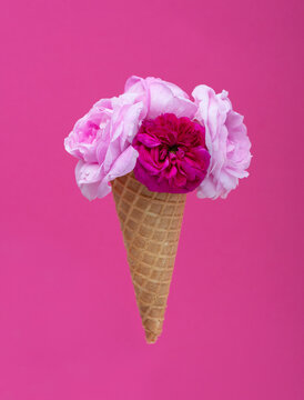 Ice cream waffle cone with a bouquet of summer flowers roses over pink background. Diet and thinking outside the box design concept
