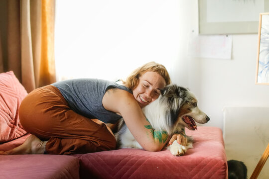 A cute red-haired girl artist is hugging on the couch together with the Aussie dog, Australian Shepherd breed. Owner and pet together in a bright, cozy living room