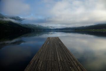 曇り空が映り込む湖と木目の桟橋