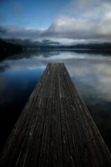 空に浮かんだ一本橋のような、湖の映り込みと桟橋