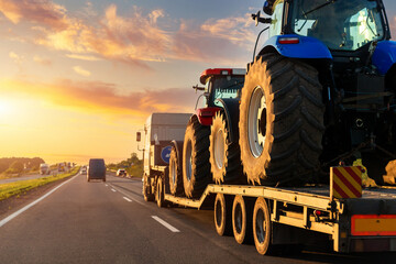 POV heavy industrial truck semi trailer flatbed platform transport two big modern farming tractor machine on common highway road at sunset sunrise sky. Agricultural equipment transportation service