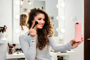 Beautiful brunette woman taking selfie photo while applying makeup in front of mirror.