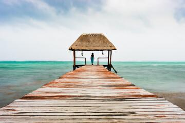 woman on pier long exposure moody Caribbean