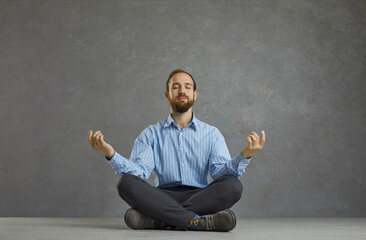 Finding zen and peace during stressful work day: Portrait of happy relaxed calm young businessman or office worker sitting in cross legged lotus yoga pose on floor, meditating and relieving stress