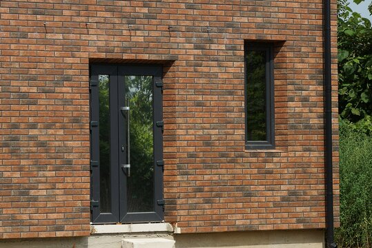 the wall of a private brown brick house with a black plastic glazed door and a window on the street