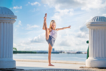 Gymnast teenage girl posing on embankment against background of the sea and sky