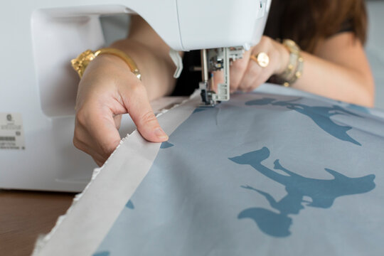 Closeup of woman's hands sewing fabric with electric sewing machine