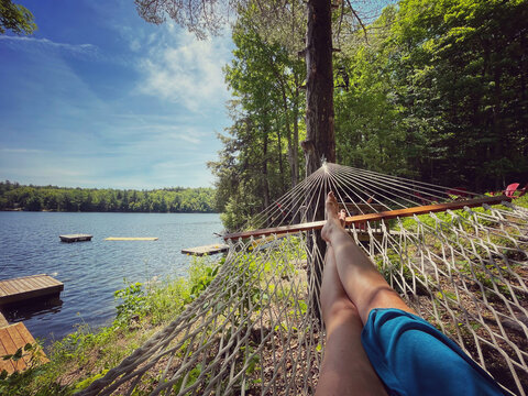 Female legs in the end of a hammock with a view of docks on a lake.